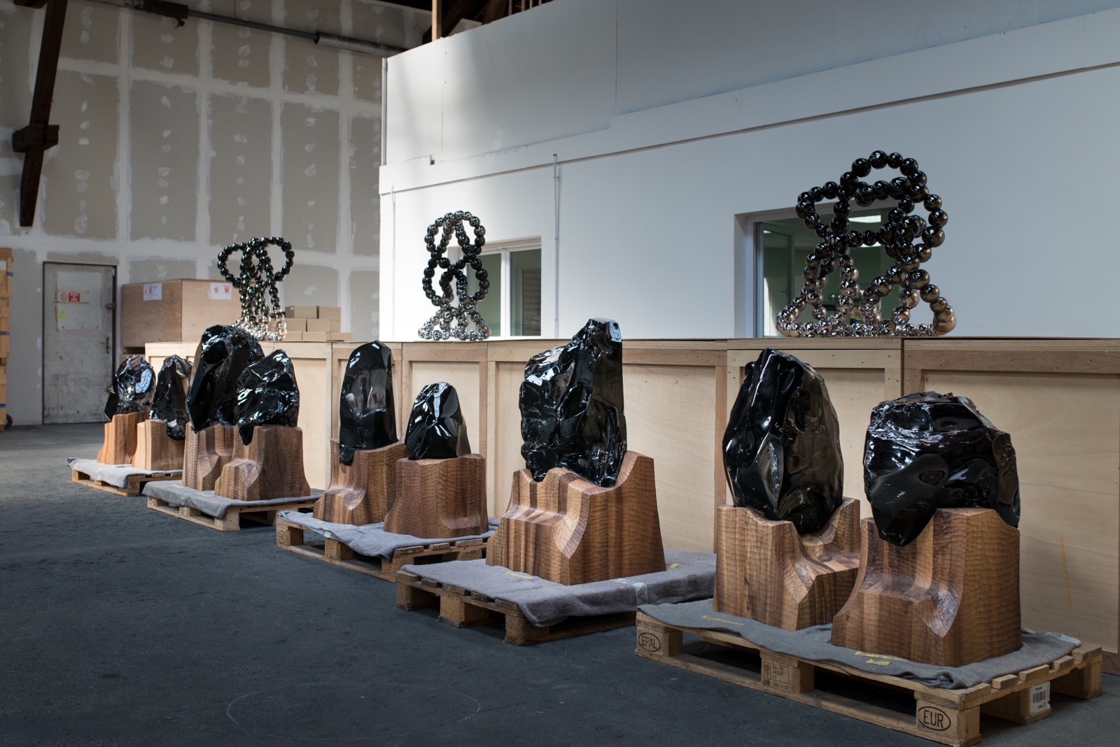 Invisibility Faces, nine quaint and primitive self-portraits made of black obsidian.